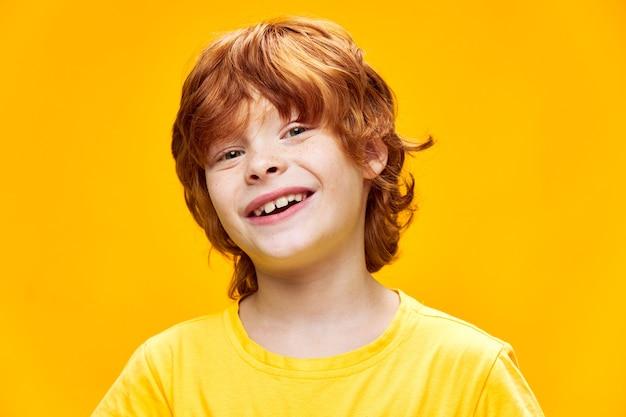 Uśmiechnięty chłopiec rude włosy żółta koszulka studio przycięty widok dzieciństwa