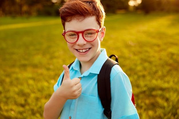 Uśmiechnięty chłopiec rudy pokazując kciuk do góry i patrząc na kamery