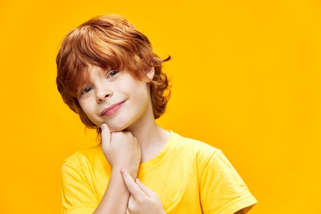 Uśmiechnięty chłopiec rudy trzymając rękę na brodzie przycięty widok studio żółty t-shirt na białym tle