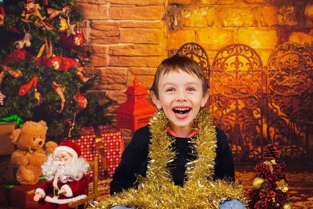 Uśmiechnięty chłopiec siedzący przy choince owinięty w błyszczące ozdoby świąteczne wesołych świąt