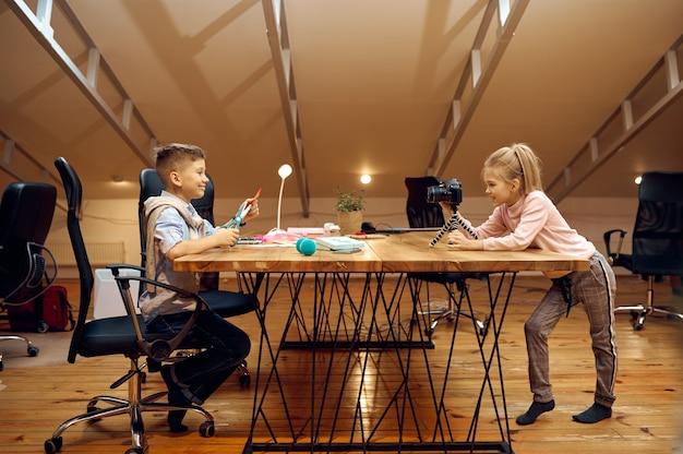 Uśmiechnięty chłopiec siedzi przy aparacie, mali blogerzy. blogowanie dzieci w domowym studio, media społecznościowe dla młodych odbiorców, transmisja internetowa w internecie