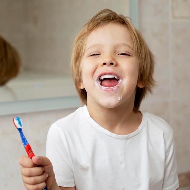 Uśmiechnięty chłopiec szczotkuje zęby