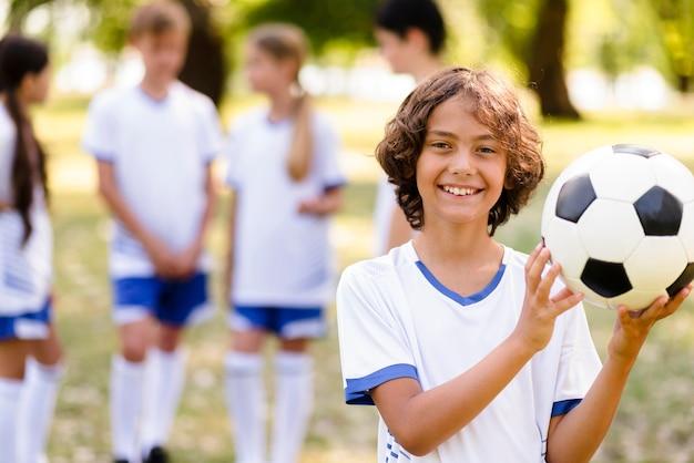Uśmiechnięty chłopiec trzyma piłkę nożną na zewnątrz