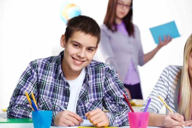 Uśmiechnięty chłopiec trzyma pióro