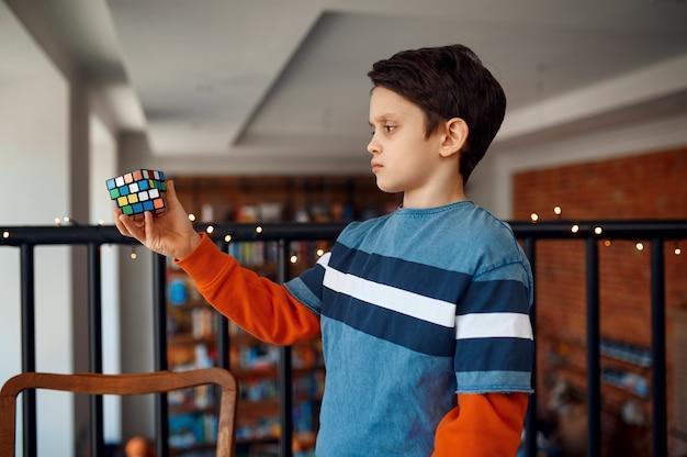 Uśmiechnięty chłopiec trzyma w rękach kostkę układanki. zabawka do treningu mózgu i logicznego umysłu, kreatywna gra, rozwiązywanie złożonych problemów