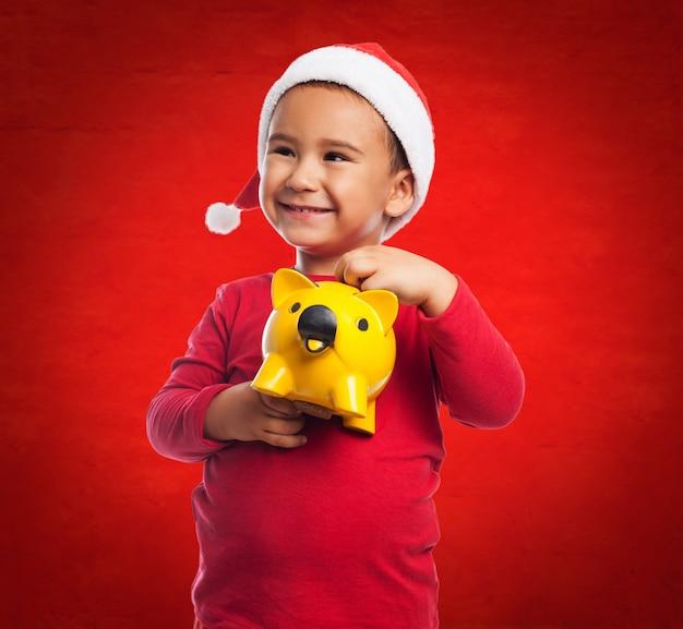 Uśmiechnięty chłopiec trzymając pieniądze na przyszłość