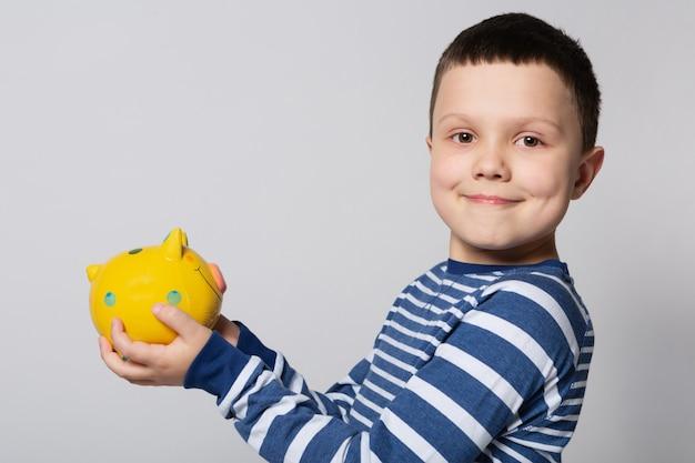 Uśmiechnięty chłopiec trzymający w rękach żółtą skarbonkę na białym tle