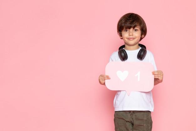 Uśmiechnięty chłopiec w białej koszulce i spodniach khaki w czarnych słuchawkach trzyma różowy znak z podobnym