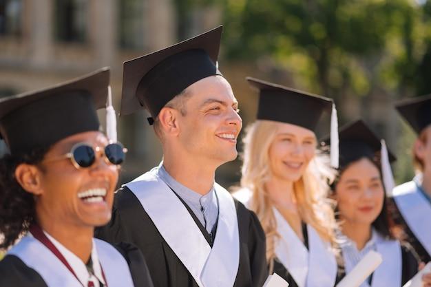 Uśmiechnięty chłopiec w czapce mistrzów stojący wśród swoich przyjaciół podczas ceremonii ukończenia szkoły