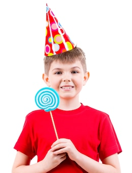 Uśmiechnięty chłopiec w czerwonej koszulce i kapeluszu strony, trzymając kolorowe cukierki - na białym tle