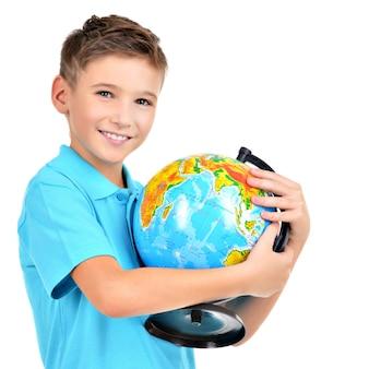 Uśmiechnięty chłopiec w dorywczo trzymając kulę ziemską w rękach na białym tle