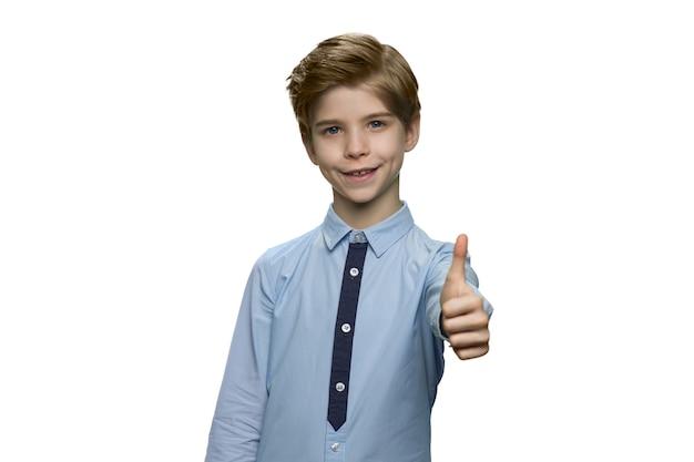 Uśmiechnięty chłopiec w niebieskiej koszuli pokazujący znak ok z kciukiem do góry