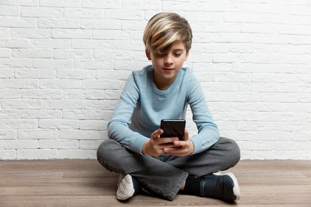 Uśmiechnięty chłopiec w niebieskim swetrze i szarych dżinsach siedzi na podłodze z telefonem na tle białej cegły