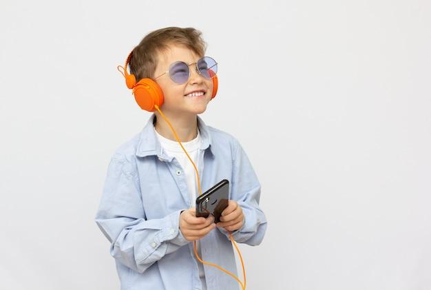 Uśmiechnięty chłopiec w okularach przeciwsłonecznych, słuchanie muzyki na słuchawkach z telefonem
