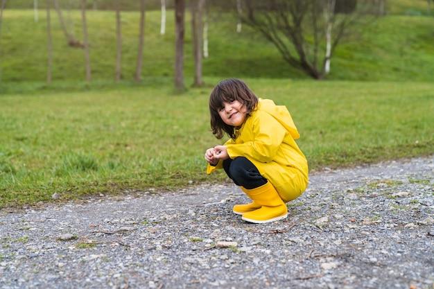 Uśmiechnięty chłopiec w płaszczu przeciwdeszczowym i żółtych kaloszach przykucnięty bawiąc się kamieniami na ziemi