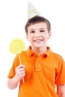 Uśmiechnięty chłopiec w pomarańczowej koszulce i kapeluszu z kolorowych cukierków - na białym tle