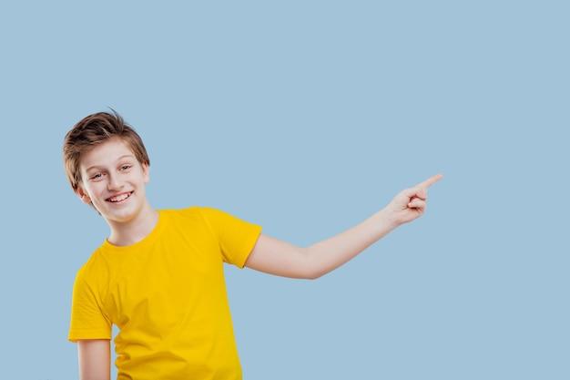 Uśmiechnięty chłopiec wskazujący palcem na lewą stronę, w żółtej koszulce na niebieskim tle