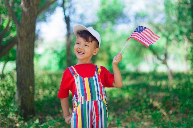 Uśmiechnięty chłopiec z dzieckiem flaga usa w jasnych ubraniach i białej czapce z flagą ameryki w dłoniach