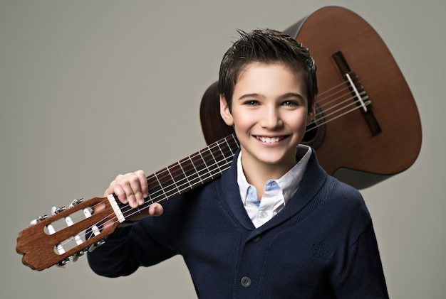 Uśmiechnięty chłopiec z gitarą.