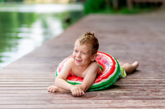 Uśmiechnięty chłopiec z kółkiem w kształcie arbuza leży latem nad jeziorem