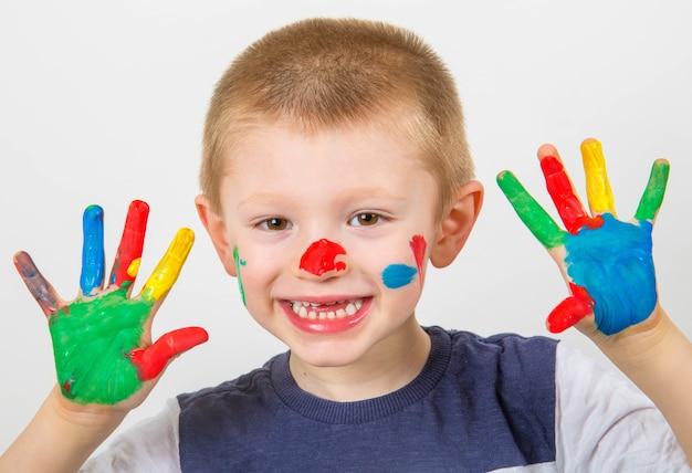 Uśmiechnięty chłopiec z rękami pomalowanymi kolorowymi farbami