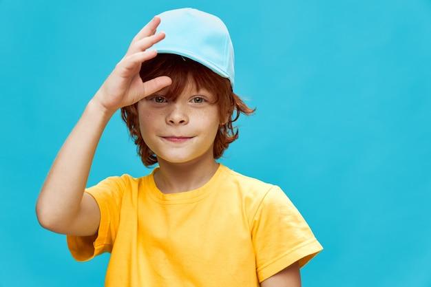 Uśmiechnięty chłopiec z rudymi włosami trzyma rękę w pobliżu jego twarzy niebieska czapka żółta koszulka niebieskie tło