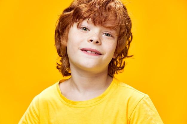 Uśmiechnięty chłopiec z rudymi włosami w żółtej koszulce na na białym tle