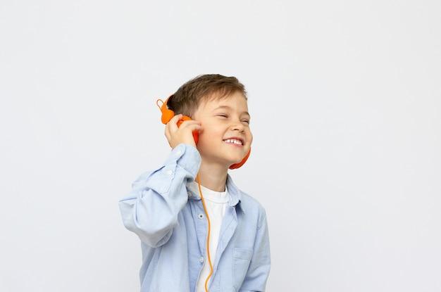 Uśmiechnięty chłopiec z zamkniętymi oczami, słuchanie muzyki na słuchawkach