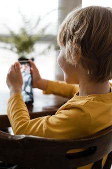 Uśmiechnięty chłopiec za pomocą smartfona w domu