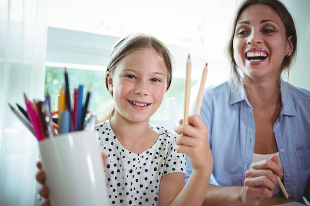 Uśmiechnięty córki obsiadanie obok matki i seansu koloru pióra