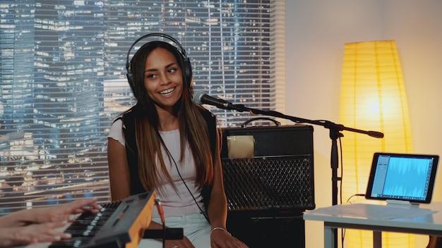 Uśmiechnięty czarny wokalista śpiewa piosenkę do mikrofonu w domowym studio nagrań