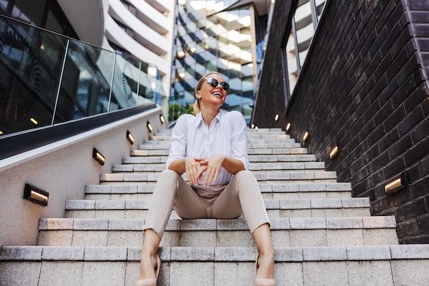 Uśmiechnięty czarujący atrakcyjny pozytywny modny blond bizneswoman siedzi na schodach w dzielnicy biznesowej.