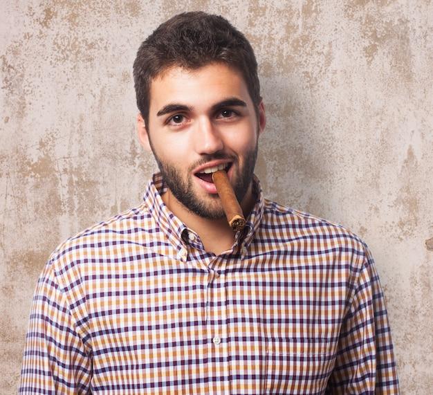 Uśmiechnięty człowiek palenia cygara.