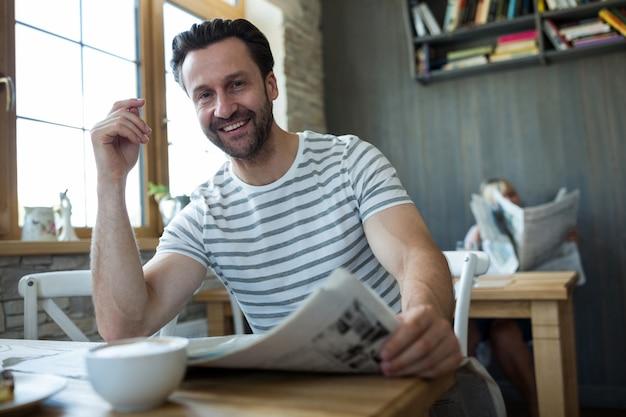 Uśmiechnięty człowiek siedzi z gazetą w kawiarni