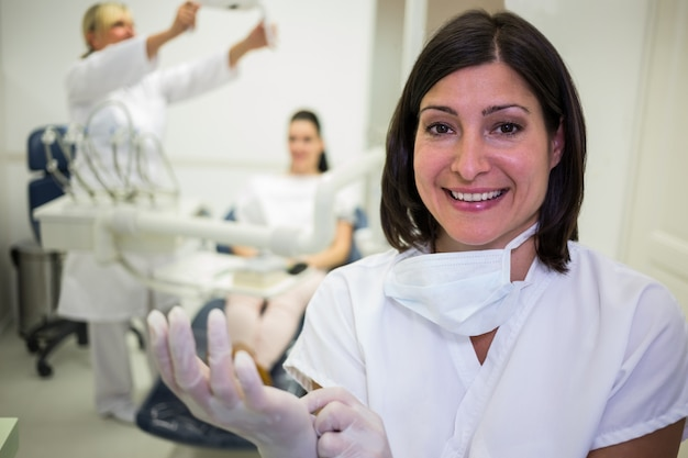 Uśmiechnięty dentysta jest ubranym rękawiczki chirurgiczne