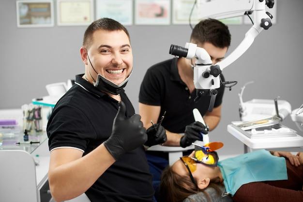 Uśmiechnięty dentysta przy głowie pacjenta patrzy z uśmiechem na kamerę i pokazuje gest palcem klasy obok stojącego asystenta. nowoczesne gabinet dentystyczny.