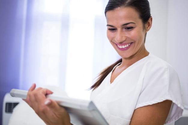 Uśmiechnięty dentysta używa cyfrową pastylkę