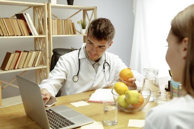 Uśmiechnięty dietetyk pokazujący pacjentowi plan zdrowej diety. młoda kobieta odwiedzająca lekarza w celu uzyskania zaleceń żywieniowych. pojęcie zdrowego stylu życia i żywności, medycyny i leczenia.