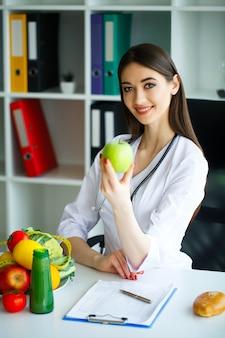 Uśmiechnięty dietetyk w jej biurze