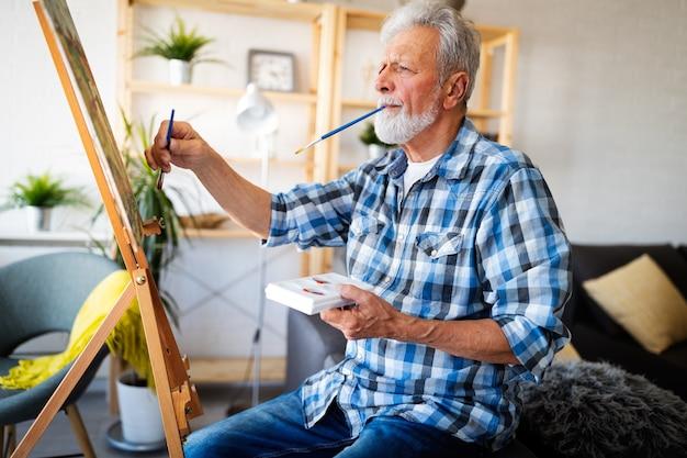 Uśmiechnięty dojrzały mężczyzna malujący na płótnie w domu
