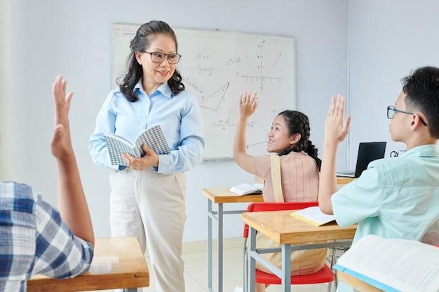 Uśmiechnięty dojrzały nauczyciel przedmiotów ścisłych zadający pytanie i patrząc na uczniów podnoszących ręce i chcących odpowiedzieć