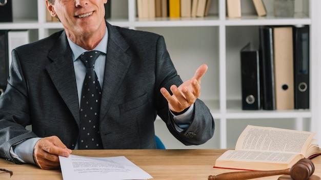 Uśmiechnięty dojrzały prawnik dyskutuje w pokoju sądowym