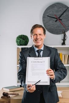 Uśmiechnięty dojrzały prawnik wskazuje przy podpisu miejscem na kontrakta dokumencie