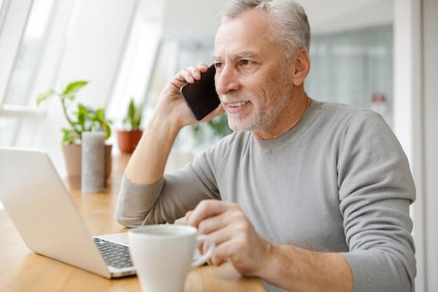 Uśmiechnięty dojrzały starszy biznesmen siedzieć w kawiarni rozmawiając przez telefon komórkowy przy użyciu komputera przenośnego.
