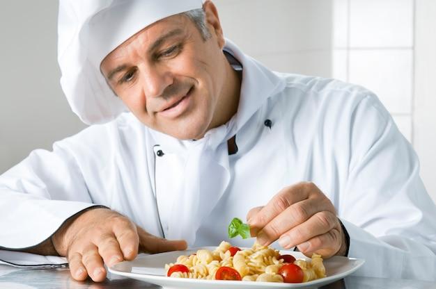 Uśmiechnięty dojrzały szef kuchni z satysfakcją przygotowuje włoskie danie z makaronu