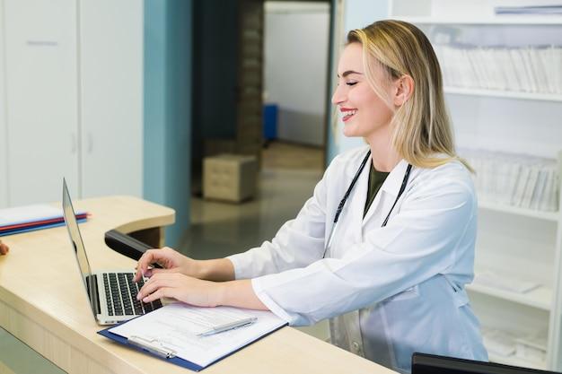 Uśmiechnięty doktorski działanie z laptopem