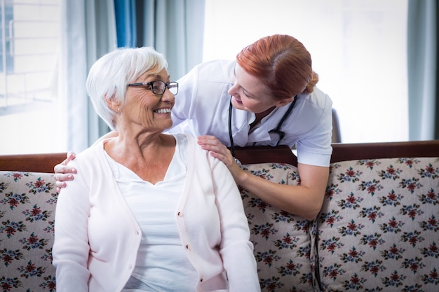 Uśmiechnięty doktorski opowiadać szczęśliwa starsza kobieta