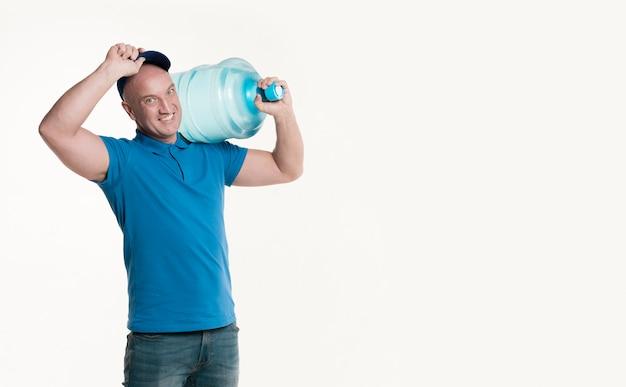 Uśmiechnięty doręczeniowy mężczyzna trzyma bidon i nakrętkę
