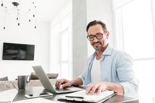 Uśmiechnięty dorośleć mężczyzna pracuje z dokumentami