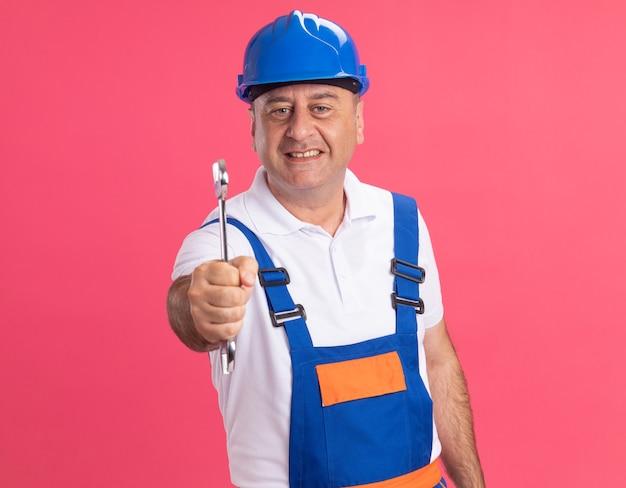 Uśmiechnięty dorosły kaukaski mężczyzna budowniczy w mundurze trzyma klucz na białym tle